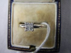 An 18ct white gold square set 4 stone diamond ring, size L half.