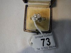 A 14 ct white gold and diamond cross over ring, size M.