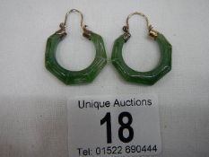 A good pair of jade earrings with possibly gold mounts.