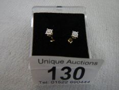 A pair of yellow gold ear studs with white stones.