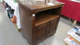 An oak cabinet with linen fold doors.