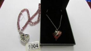 A Fiorelli heart pendant in silver and a heart pendant in shades of pink,