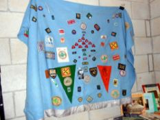 An old scouts blanket with large quantity of scouting badges sewn on