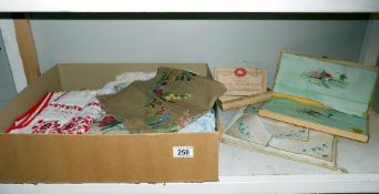 A box of vintage textiles including embroidered household linens.