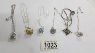 6 assorted silver pendants.