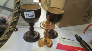 A pair of coconut shell goblets on turned stems and a hat pin stand.