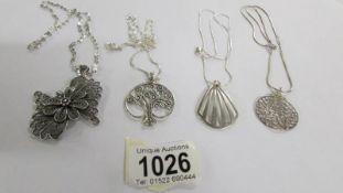 4 assorted silver pendants.