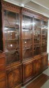 A good mid 20th century feathered mahogany break front bookcase in good condition.