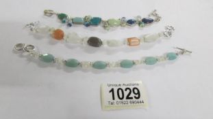 Three silver and coloured stone bracelets.
