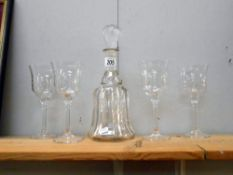 A glass decanter and 4 long stemmed wine glasses