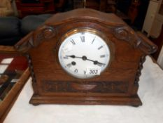 A 1930's oak 8 day mantle clock with enamel dial