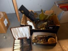 A box of assorted brassware, including boxed set of fish knives and forks, trivet, old tin,