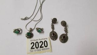 A pair of silver pendant earrings and a silver pendant with matching earrings.
