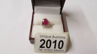An 18ct gold shield shaped ruby ring surrounded by diamonds, size O, total approximate weight 3.
