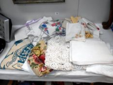 A box of household textiles including embroidered linens,