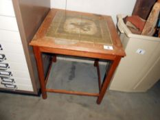 A small coffee table with tiled top depicting a bird (in need of a clean)
