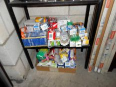 A large quantity of various sized light bulbs on 2 shelves plus strip lights,