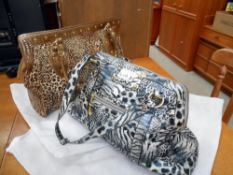 2 Butler and Wilson handbags being a leopard print and one other animal print.