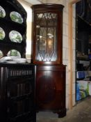 A darkwood stained corner cupboard with astragal glazed mirror back top