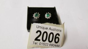 A pair of 18ct yellow gold emerald and diamond earrings.