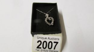 A 14ct diamond heart shaped pendant on a white gold chain, total approximate weight 3.1 grams.