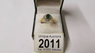An 18ct yellow gold oval emerald ring with baguette and brilliant diamonds, size Q,
