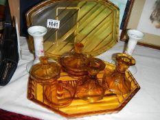 An amber glass trinket set, spare amber glass tray and pair of china candlesticks.