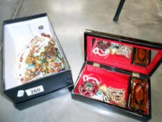 A box of costume jewellery and a black lacquered jewellery box and contents