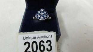 A costume ring set blue stones, size I.