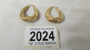 A pair of 9ct gold textured hoop earrings.