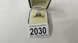 A diamond single stone ring dated Birmingham 1979 in a textured 9ct gold band with platinum mounted