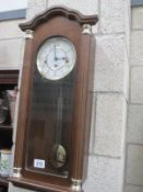 A Hermle wall clock with pendulum and key