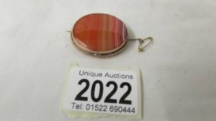 An early 20th century agate brooch stamped 9ct gold with safety chain.