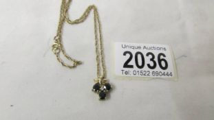 A 9ct gold 3 sapphire pendant with attached chain.