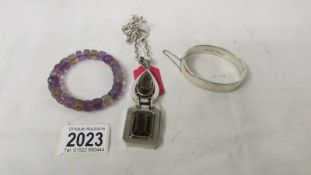 A circa 1980's silver bangle together with an amethyst and quartz bracelet and a heavy quality