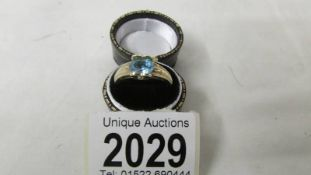 A vibrant blue topaz oval stone ring set with 2 diamonds to mount in 9ct gold, size P.