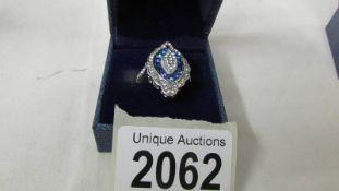 A costume ring set blue stones, size L half.