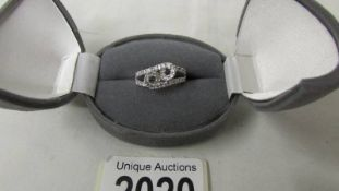 A unusual diamond ring in a twist style, stamped 9ct white gold, size N.