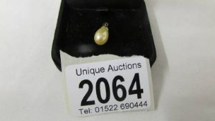 A gold mounted pearl pendant.
