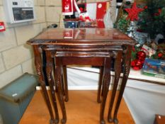 A dark wood stained nest of tables with red leather under glass tops 55cm x 42cm,