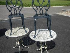 2 circular garden tables and 2 chairs.