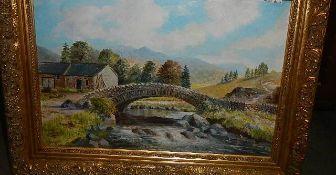 A gilt framed oil on board rural scene with stone bridge.