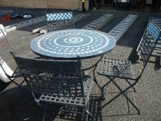 A metal garden table and chairs with tiled top.