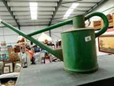 An unusually shaped green watering can
