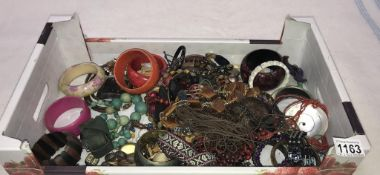 A large box of costume jewellery including bangles