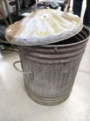 A galvanised ribbed dustbin with lid.