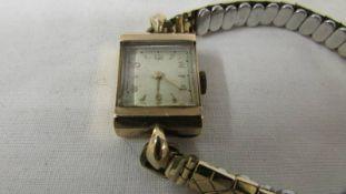 A vintage gold ladies wrist watch on a yellow metal bracelet.