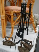 A metal companion set, 3 flat irons and a toasting fork.