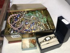 An old tin full of costume jewellery,