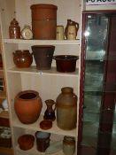 Four shelves of good earthenware pots.